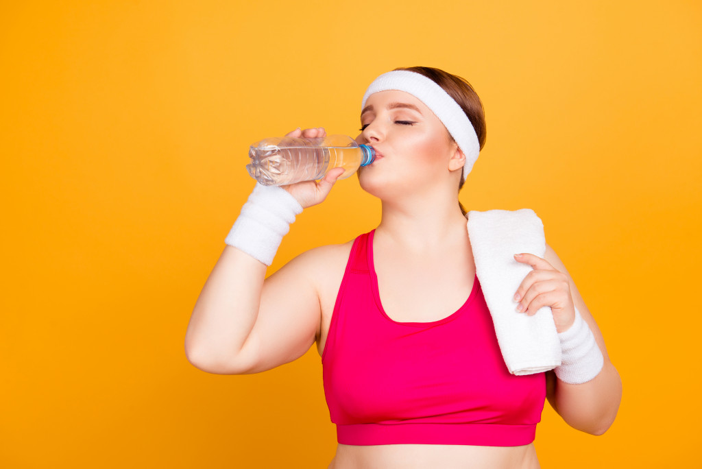 woman in working outfit driniking water