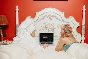 2 women watching netflix on the bed